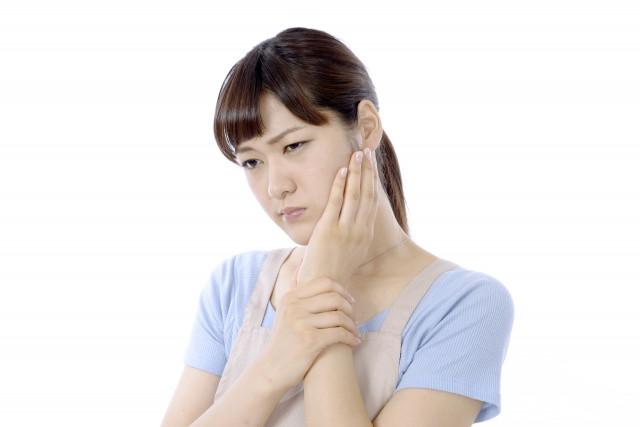顎を抑える女性の写真