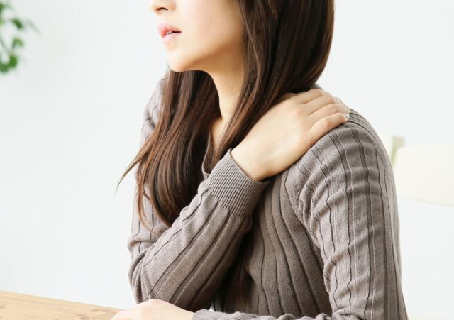 肩を抑える女性の写真
